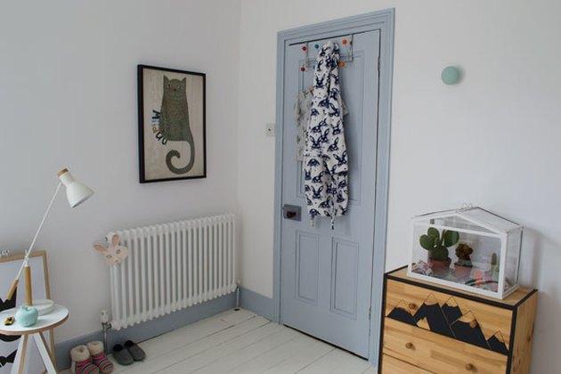 Kids' minimalist bedroom with blue door and cat wall art