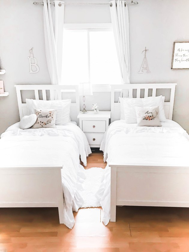 Kids' minimalist bedroom with white beds and throw pillows