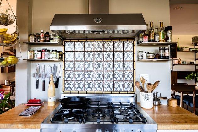 view of kitchen stove, accent backsplash and range hood