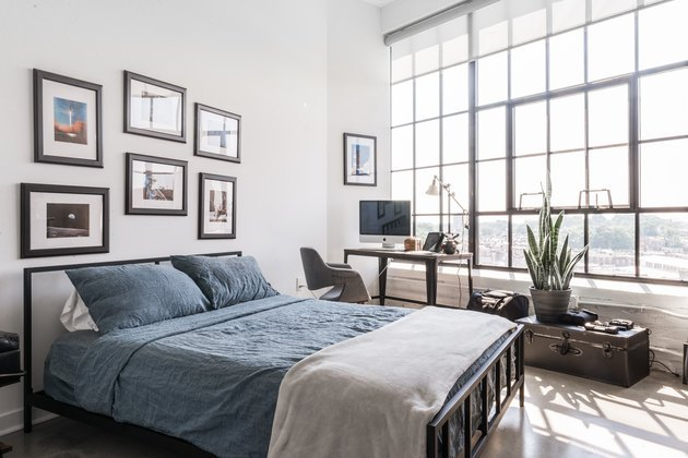 modern industrial bedroom with large steel windows and metal bed frame