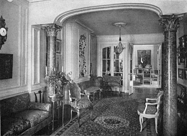 black and white photograph of interior with seating, patterned rug, and chandelier