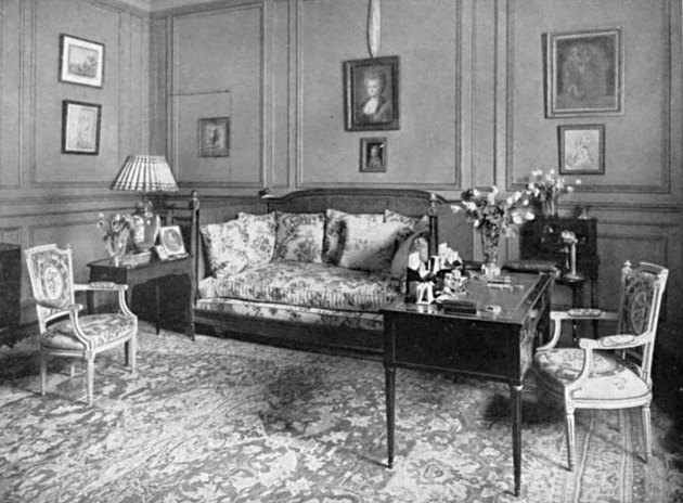 black and white photograph of a living room space with chairs, couch, and framed artworks