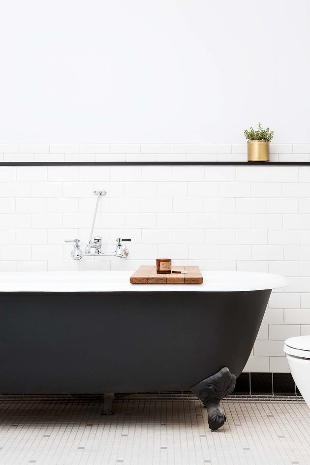 industrial chic bathroom with claw foot tub black-and-white subway tile