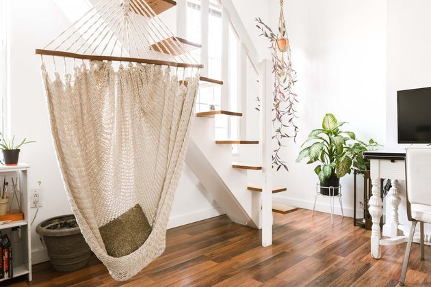 jungalow minimalism in modern apartment stairway with hanging macrame chair and plants