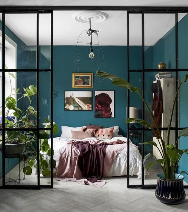bohemian teal bedroom with white ceiling and factory style doors