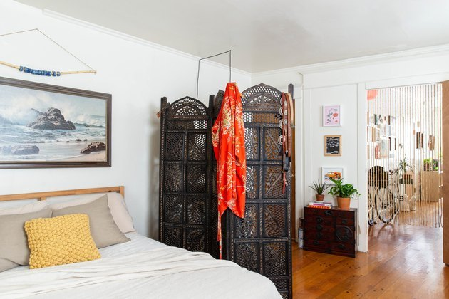 eclectic bedroom with ornate room divider screen and midcentury art