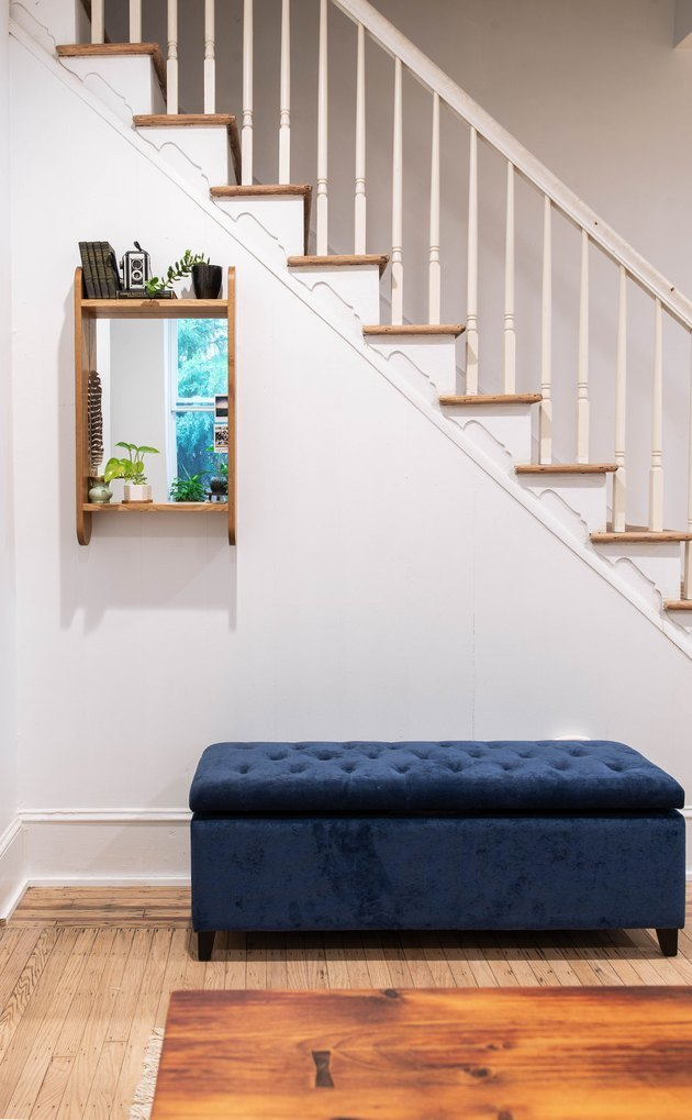 minimal entryway with oak mirror and blue velvet storage bench