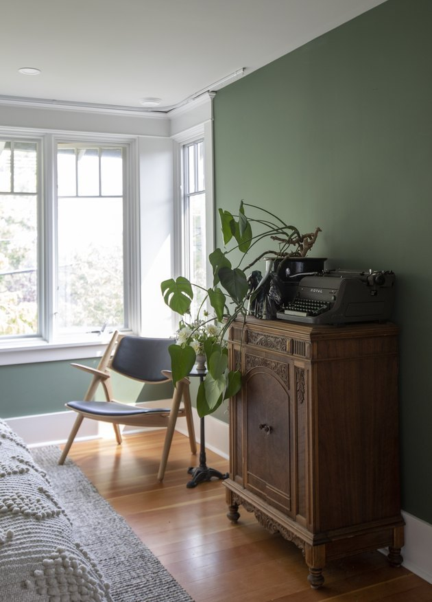 arts and crafts interior of bedroom with green wall and wood cabinet
