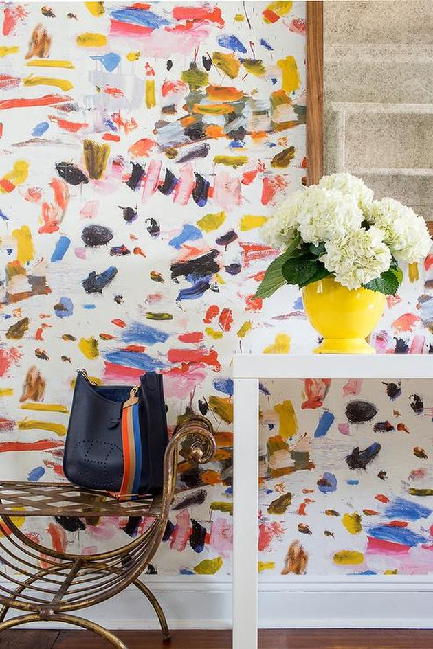 abstract modern wallpaper in entryway with yellow vase and flowers