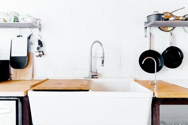 large kitchen sink, chrome faucet and hanging cast iron pans