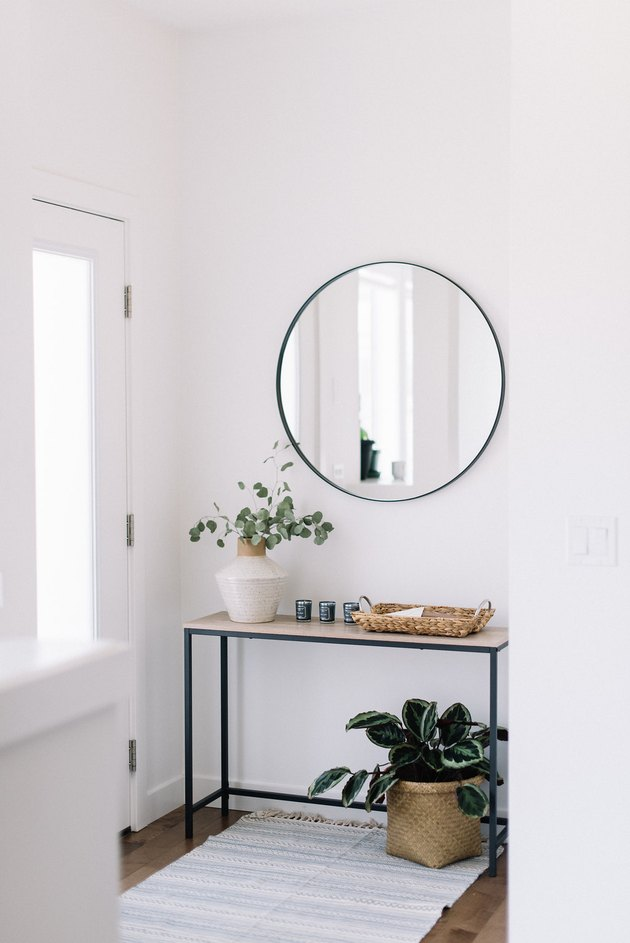 minimalist apartment ideas with white entryway and circle mirror