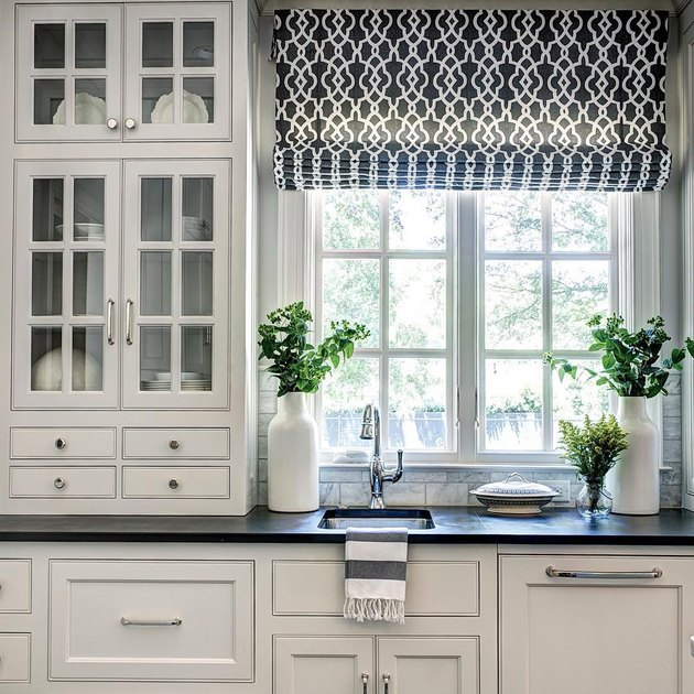 Black and white farmhouse kitchen with white cabinets and slate countertops