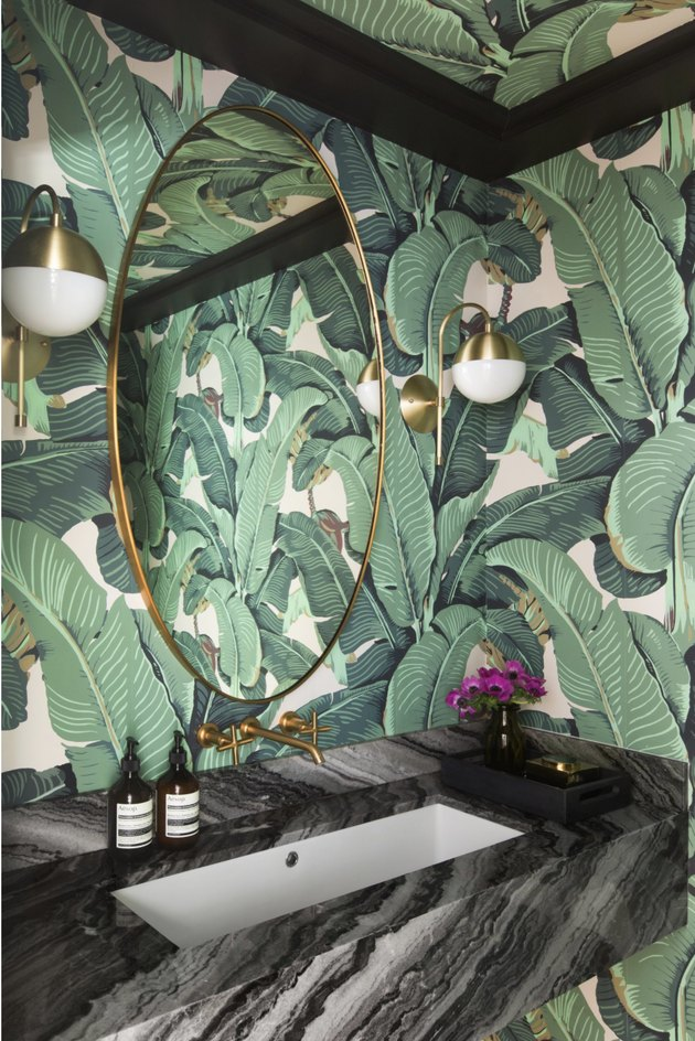 bathroom mirror lighting ideas with gold sconces and botanical print wallpaper