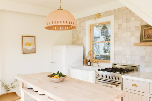 light kitchen, natural tile backsplash and earth-tone pendant light