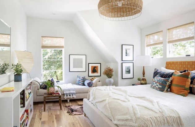 studio bedroom idea for bright and airy second-floor bedroom with white bedding, a white shelf, and a beige chaise lounge in the window