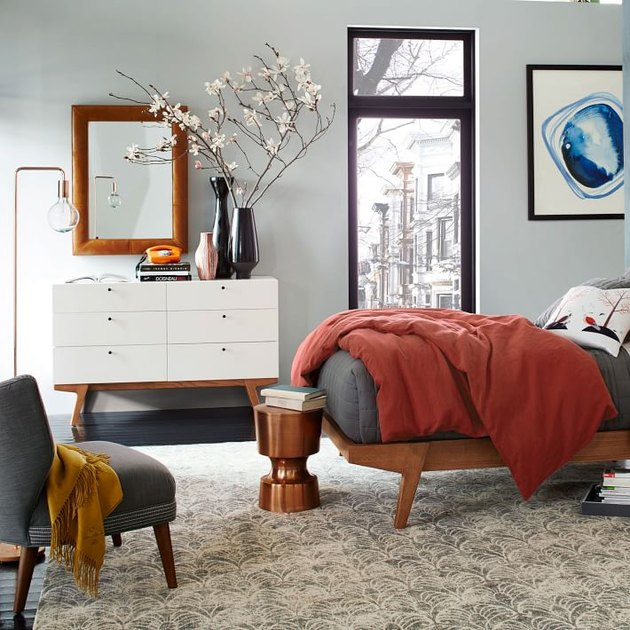 modern studio bedroom idea with light gray walls, a mid-century-style wood bed with gray and rust bedding, and a white mid-century style dresser