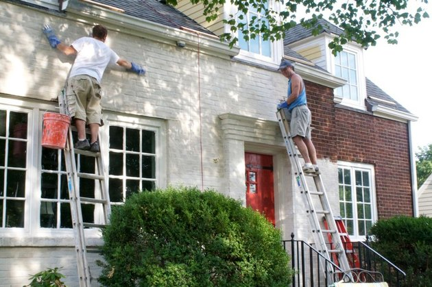 Men painting a brick house