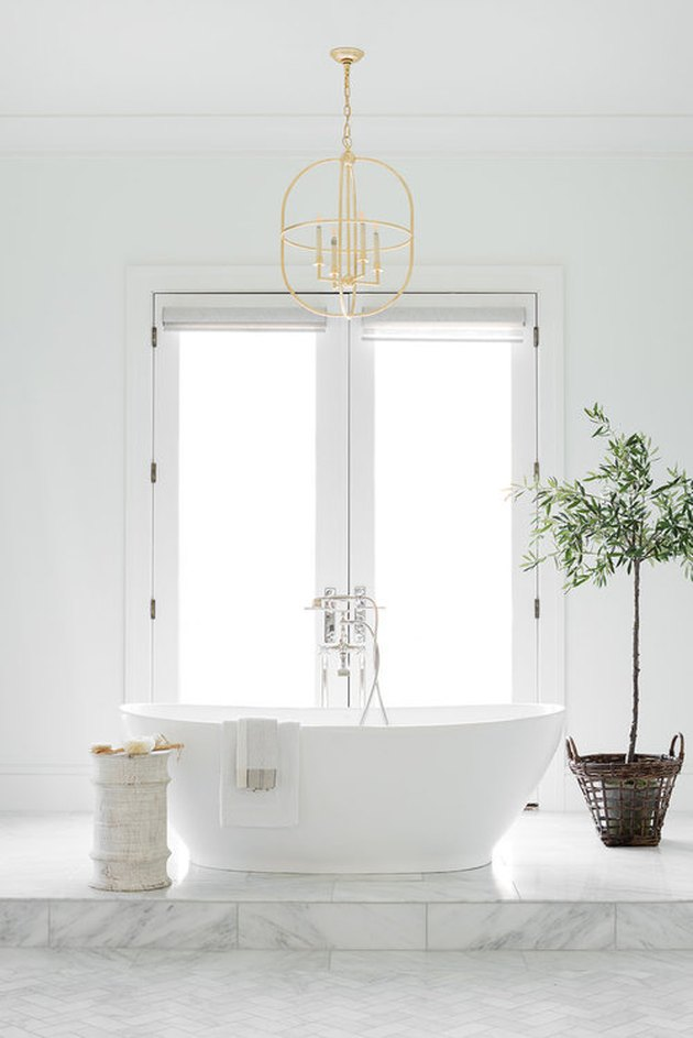 white bathroom idea with freestanding tub on raised platform and French doors