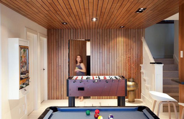 basement game room ideas with wood paneled ceiling and accent wall and pool table
