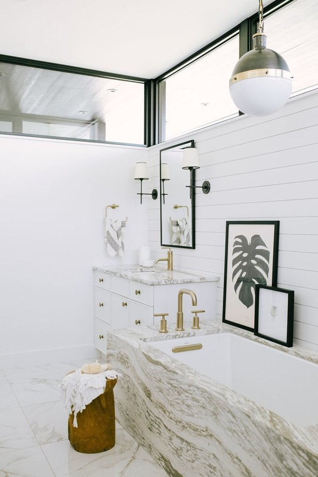 white bathroom idea with marble tub surround and shiplap wall