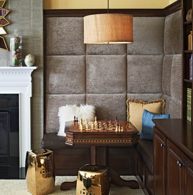 basement game room ideas with cheese table, padded walls, cane pendant lamp, white mantle, throw pillows.