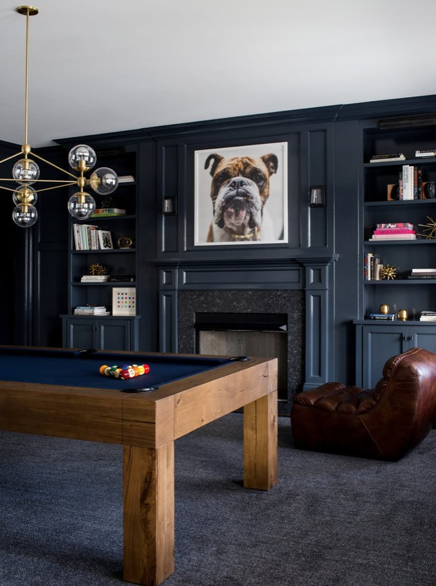 basement game room ideas with dark gray pool room, modern pool table, brass modern chandelier, leather lounge chair, built in book shelves, fireplace.