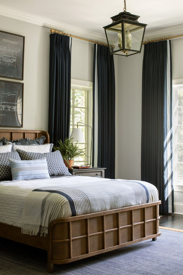 Traditional bedroom with navy blue curtains and lantern-style pendant light