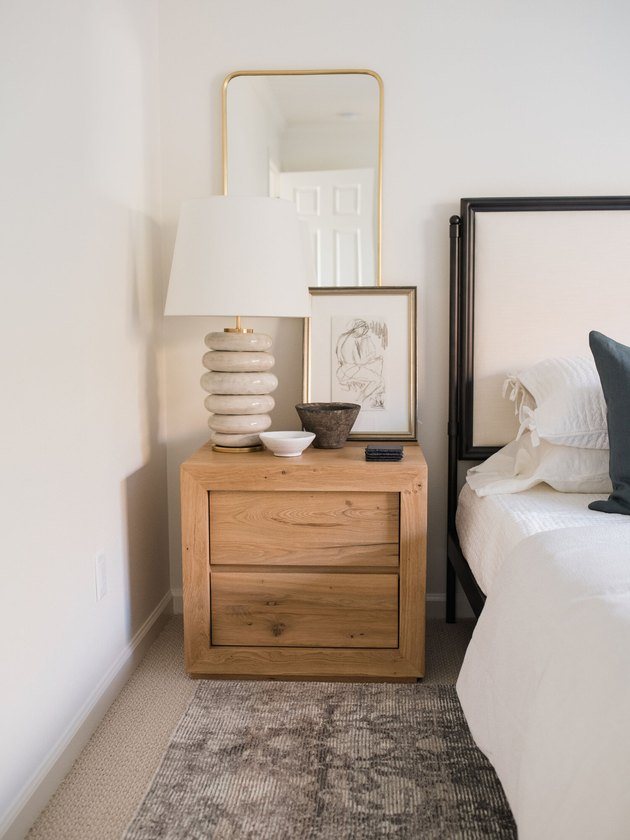 Traditional bedroom with modern lamp and artwork on nightstand