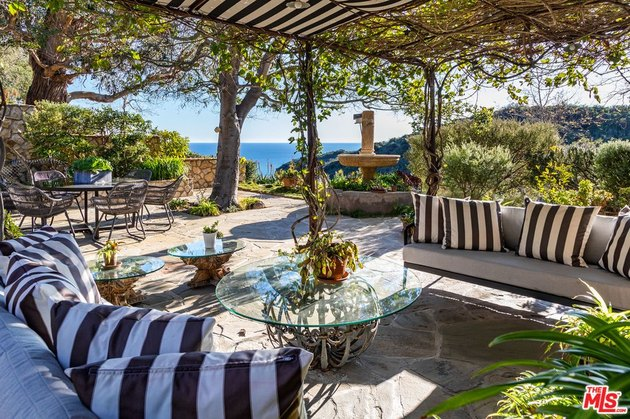 outdoor patio area with ocean view in the distance