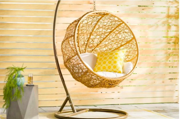 Hanging birdnest chair on stand side table with plant
