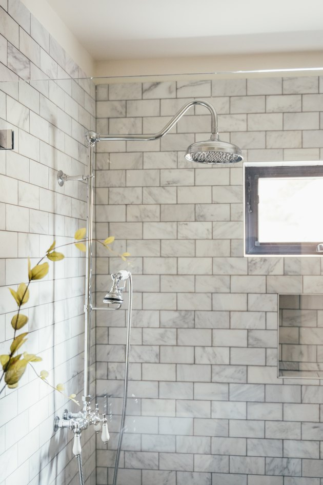 shower with glass wall and grey subway-tile backsplash
