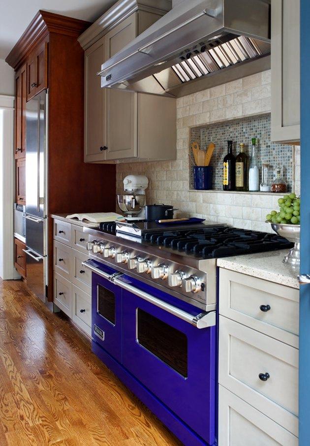 travertine kichen backsplash in kichen with a blue stove and multi-tone cabinets