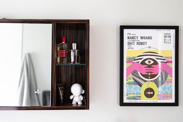 close up of art and dark wood bathroom medicine cabinet