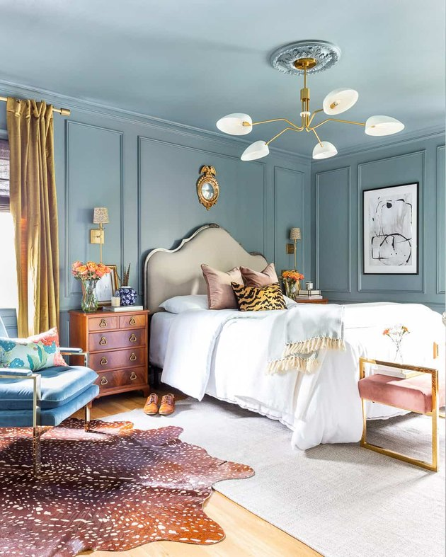 traditional bedroom with blue walls and ceiling and layered rugs and floor to ceiling drapery
