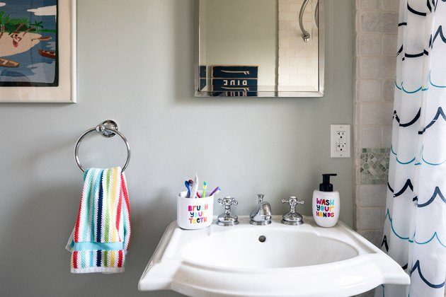 pedestal sink and mirror, colorful towel, toothbrush holder and soap dispenser for kids' bathroom
