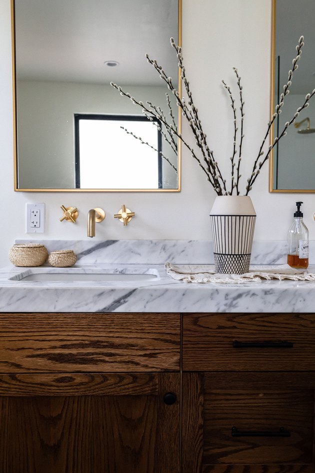 bathroom vanity and sink, wall-mounted brass faucet, rectangular mirror with gold trim and decorations