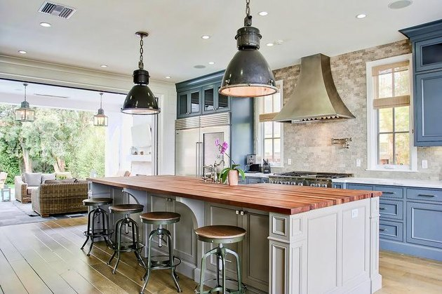 travertine backsplash in traditional industrial kitchen with butcher block island and blue cabinets
