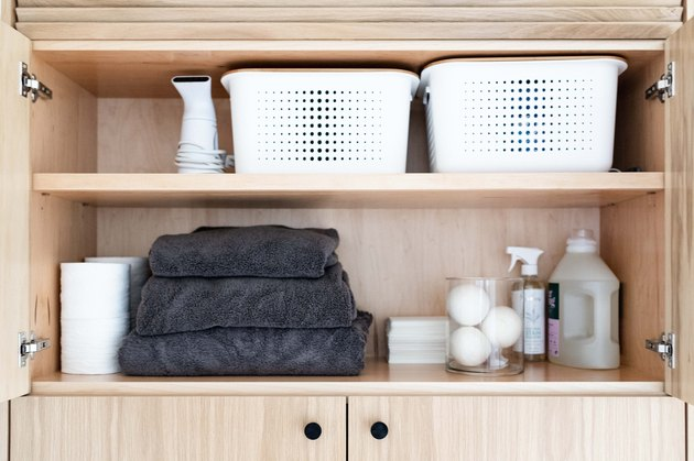 cabinet storage with storage baskets, cleaning supplies and towels