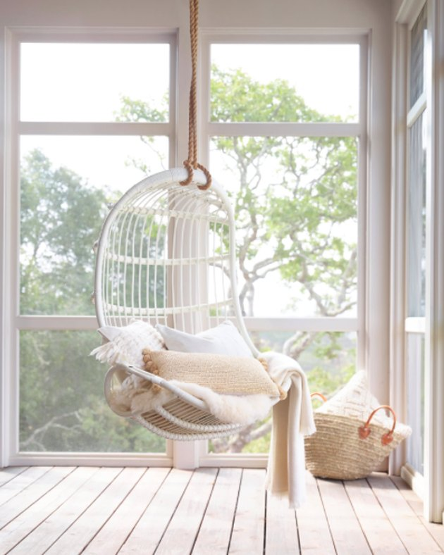 Sun porch, white pillows, large windows, hanging rattan white chair