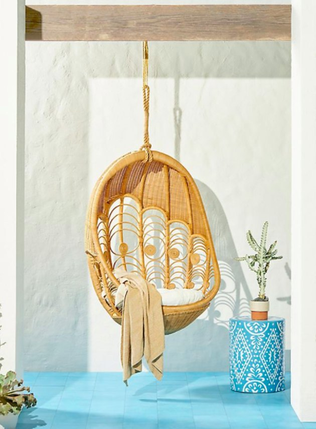 hanging peacock patterened wicker chair blue floor tile side table