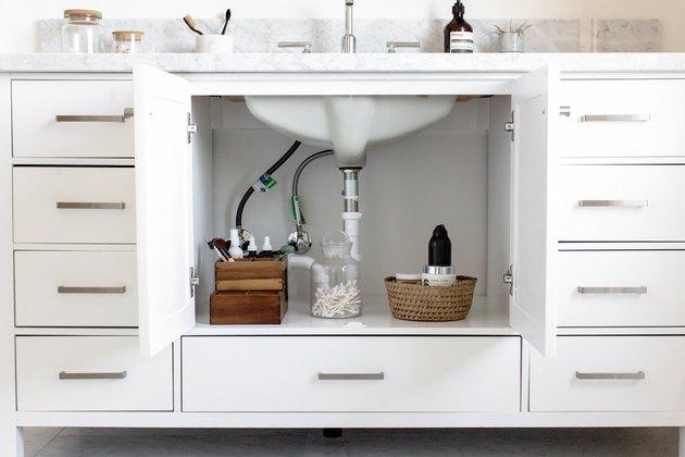 white bathroom vanity with doors open, exposed sink plumbing
