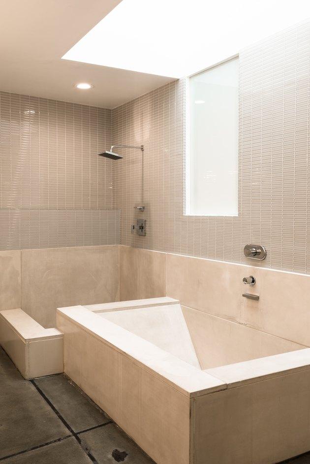 modern glass tile shower and open bath, light fixture overhead