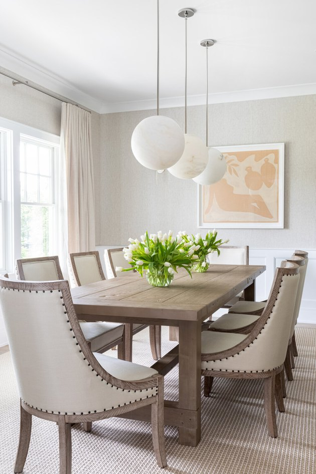 white traditional dining room with wooden table and globe pendant lights