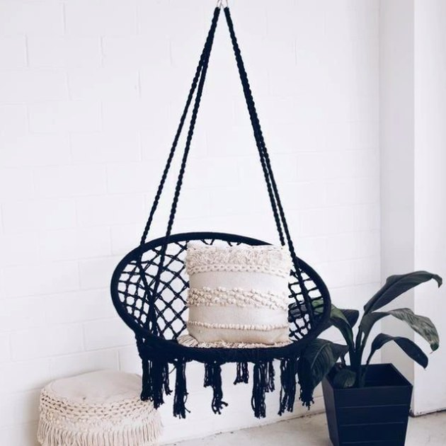 black hanging boho chic chair with fringe white pillow and plant