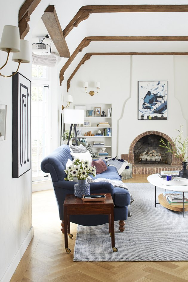 Built-in living room shelving idea near brick fireplace and exposed beams