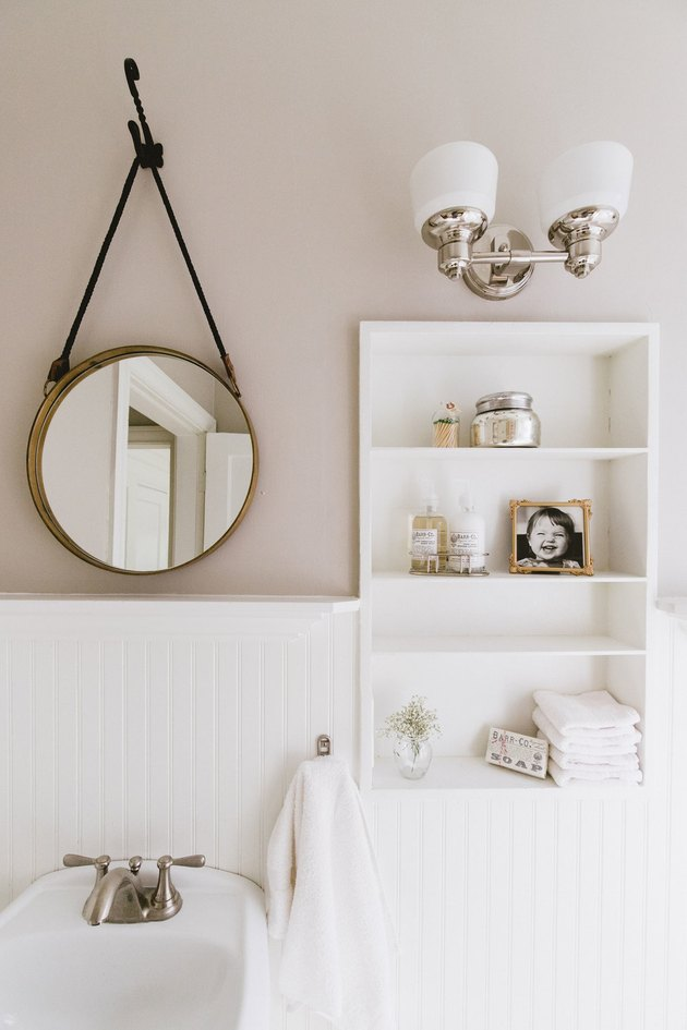 bathroom towel storage idea in white bathroom with round mirror and built-in shelving