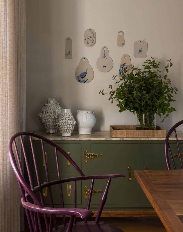 Taupe color in dining room with purple chairs and green buffet
