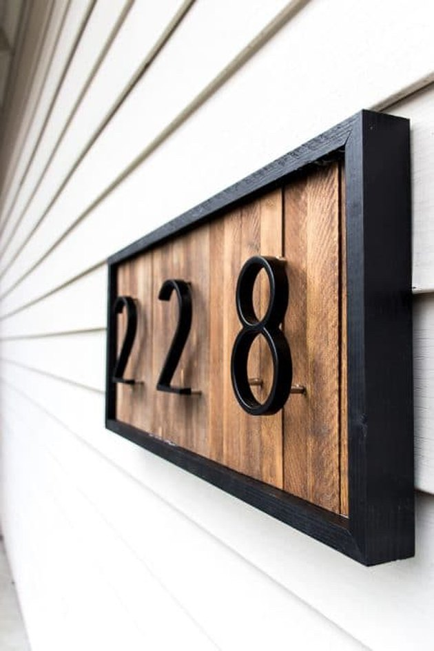 modern DIY house number sign with wood background and black frame