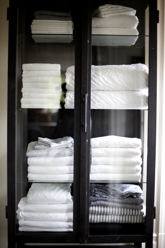wood cabinet with glass doors for bathroom towel storage idea