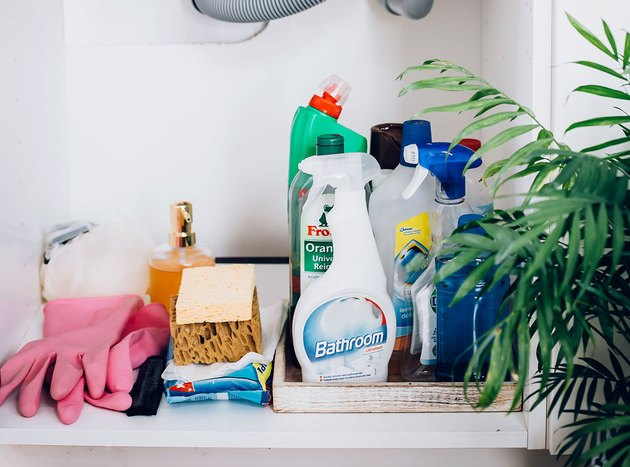 cleaning product bottles, sponges, and pink rubber gloves underneath bathroom sink